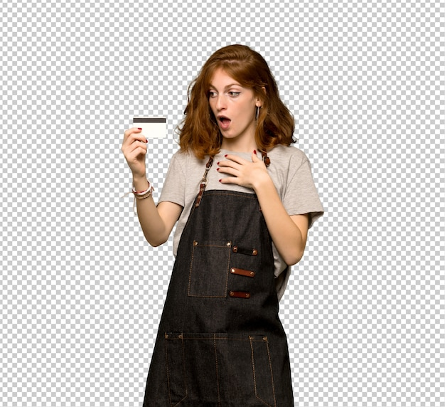 Mulher jovem ruiva com avental segurando um cartão de crédito e surpreso