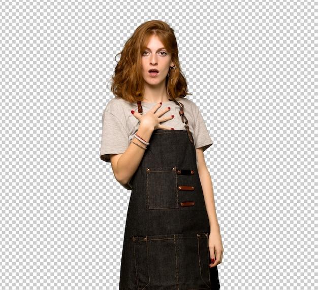 Mulher jovem ruiva com avental surpreso e chocado ao olhar para a direita