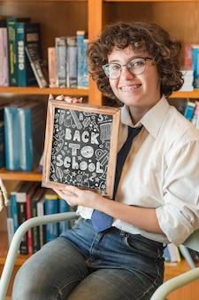 Mulher jovem, segurando, slate, mockup, em, biblioteca