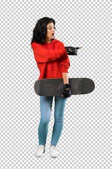 Mulher jovem skatista surpreso e apontando o lado