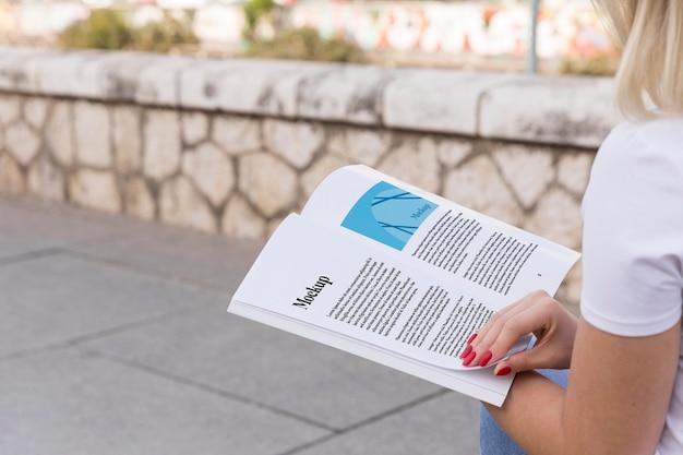 Mulher lendo livro na rua de perto