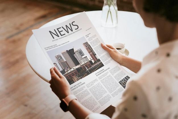 Mulher lendo uma maquete de jornal