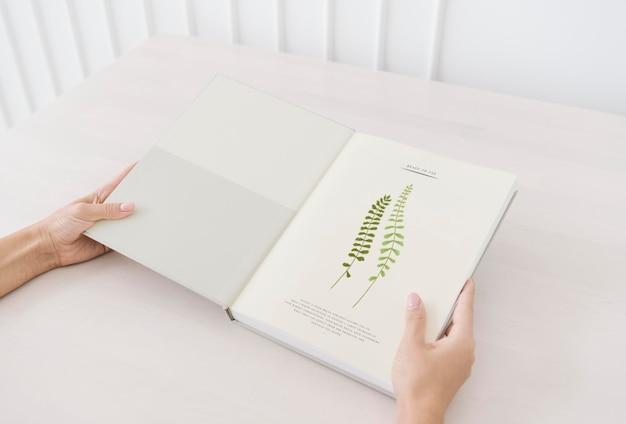 Mulher lendo uma maquete de livro botânico