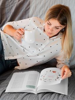 Mulher lendo uma revista e segurando uma caneca