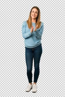 Mulher loira com camisa azul aplaudindo após apresentação em uma conferência