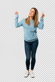 Mulher loira com camisa azul, apontando com o dedo indicador uma ótima idéia