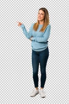 Mulher loira com camisa azul, apontando o dedo para o lado em posição lateral