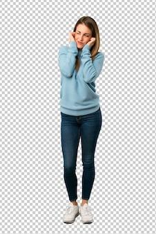 Mulher loira com camisa azul, cobrindo as orelhas com as mãos. expressão frustrada
