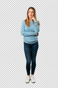 Mulher loira com camisa azul com dúvidas enquanto olhando para cima