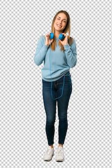 Mulher loira com camisa azul com fones de ouvido