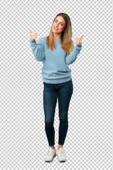 Mulher loira com camisa azul dando um polegar para cima gesto com as duas mãos e sorrindo