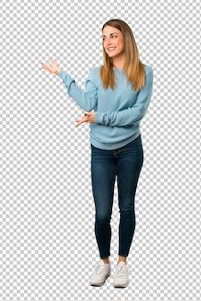 Mulher loira com camisa azul, estendendo as mãos para o lado para convidar para vir