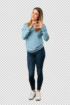 Mulher loira com camisa azul fazendo o símbolo do coração pelas mãos