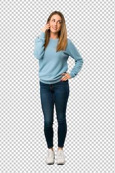 Mulher loira com camisa azul, mantendo uma conversa com o telefone móvel