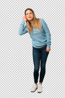 Mulher loira com camisa azul, ouvindo algo, colocando a mão sobre a orelha