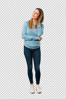 Mulher loira com camisa azul, pensando uma idéia enquanto coçando a cabeça