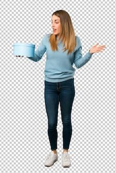 Mulher loira com camisa azul, segurando a caixa de presente nas mãos