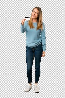 Mulher loira com camisa azul segurando um cartão de crédito