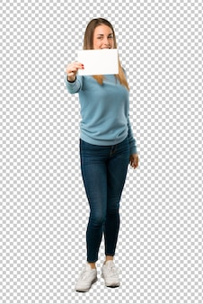 Mulher loira com camisa azul, segurando um cartaz branco vazio