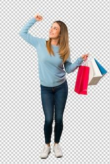 Mulher loira com camisa azul segurando um monte de sacolas de compras em posição de vitória