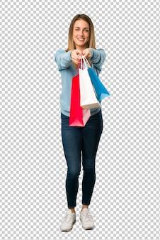 Mulher loira com camisa azul, segurando um monte de sacos de compras