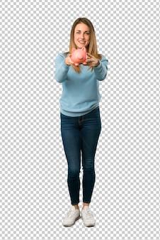 Mulher loira com camisa azul, segurando um piggybank