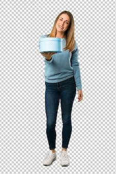 Mulher loira com camisa azul, segurando um presente nas mãos