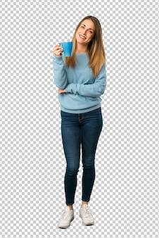 Mulher loira com camisa azul, segurando uma xícara de café quente