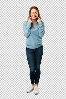 Mulher loira com camisa azul, sorrindo com uma expressão feliz e agradável