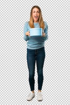 Mulher loira com camisa azul surpresa porque foi dado um presente