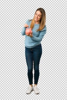 Mulher loira com camisa azul tomando um cofrinho e feliz porque está cheio
