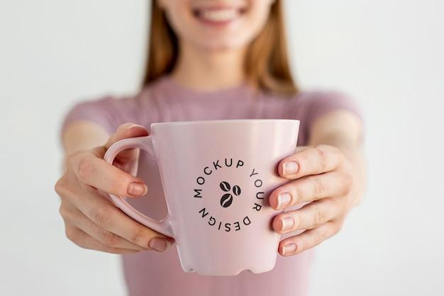 Mulher loira com maquete de caneca de café
