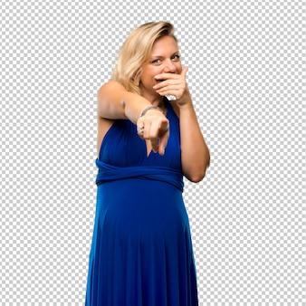 Mulher loira grávida com vestido azul, apontando com o dedo para alguém e rindo muito