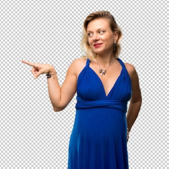 Mulher loira grávida com vestido azul, apontando o dedo para o lado e apresentando um produto