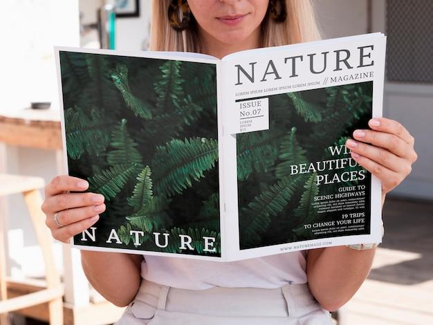Mulher loira olhando para uma revista de natureza simulada