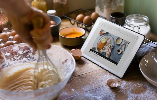 Mulher mexendo enquanto olha para uma receita em um tablet