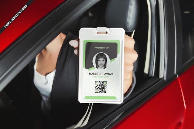 Mulher mostrando cartão de identificação da maquete da janela do carro