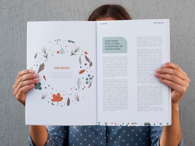 Mulher mostrando um livro aberto simulado acima