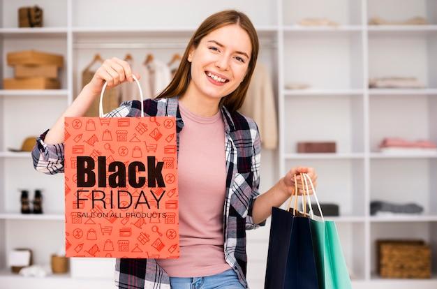 Mulher mostrando um saco de papel preto sexta-feira