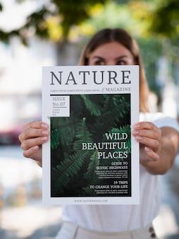 Mulher mostrando uma revista natureza mock up