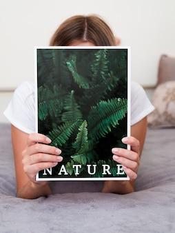 Mulher na cama segurando uma revista de natureza