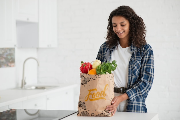 Mulher na cozinha com saco de legumes frescos
