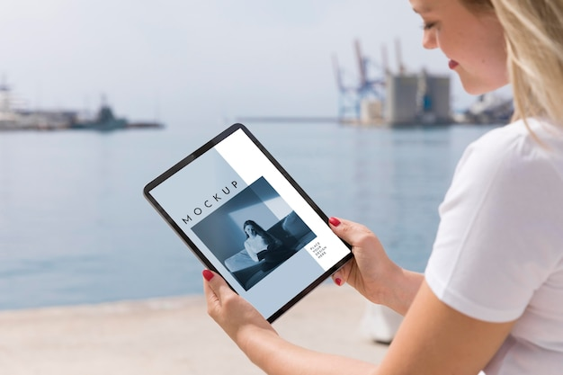 Mulher na rua lendo livro no tablet