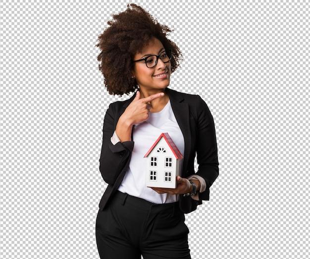 Mulher negra de negócios segurando uma casa pequena