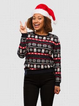 Mulher negra nova em uma camisola na moda do natal com a cópia divertimento e feliz fazendo um gesto da vitória