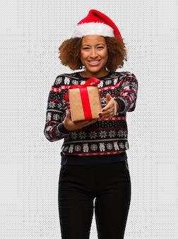 Mulher negra nova que guarda um presente no dia de natal que alcança para fora para cumprimentar alguém