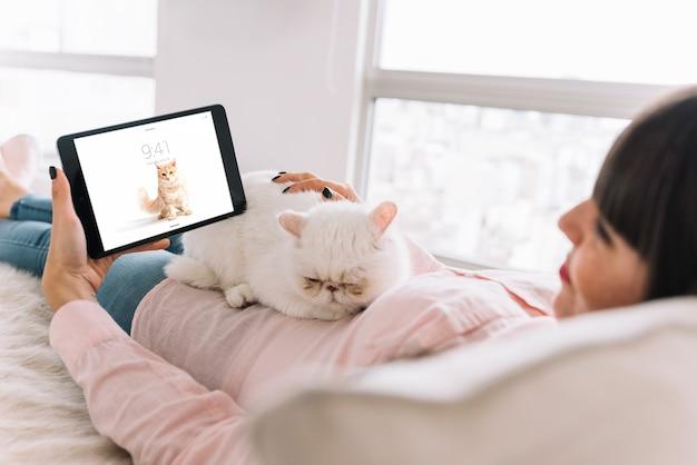 Mulher no sofá com gato e tablet maquete