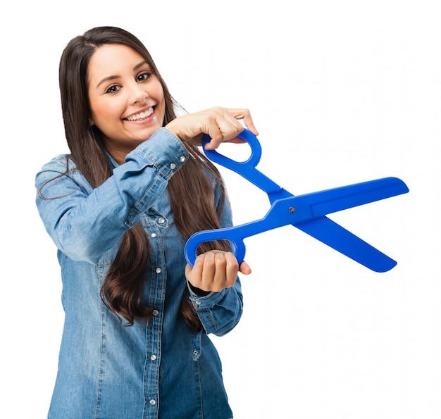 Mulher nova que prende um azul tesoura de plástico