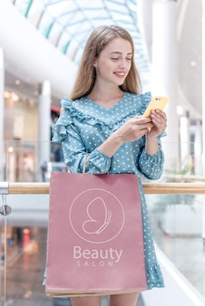 Mulher olhando para o celular em shopping
