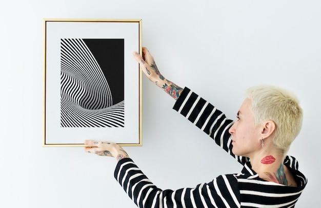 Mulher pendurando um porta-retratos em uma parede branca